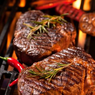 steaks grilling on hot coals