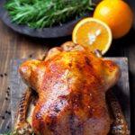roast cornish hen on a boar with orange slices